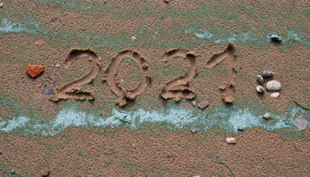 A small red stone - the heart and numbers of 2021 on the sand. Summer beach holidays. The message is handwritten. The concept of a New year.