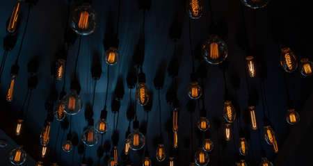 Retro Edison lamp on a black background of the ceiling. Concept idea