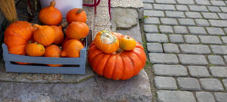 Orange pumpkins of various sizes lie on the porch of the house. The Concept Of Halloween.