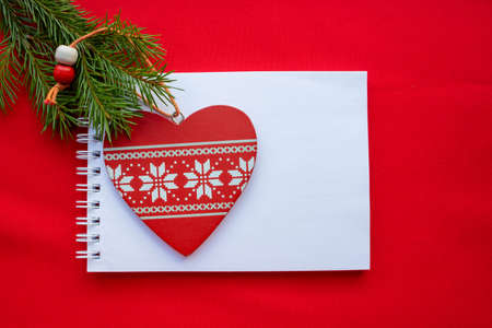 Festive composition Notepad, red wooden heart with white ornament and green fir branches on a red background. Christmas and Valentine's day concept.