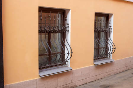Facade on the side. Windows with iron bars with the ligature.