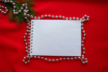 Composition - Notepad and green spruce branches with silver beads on a red background. New year's concept of Christmas.
