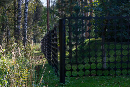 Black metal fence grating with round holes.