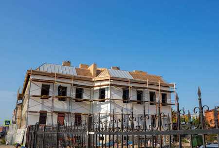A house under construction with scaffolding against a blue sky