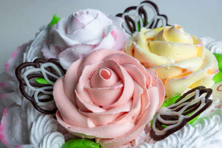 Sweet cream on the cake in the form of colorful roses.