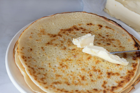 Pancakes on a plate with butter on the table