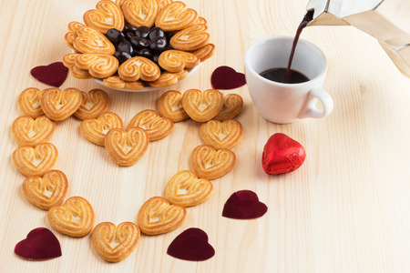 Espresso coffee is poured into a cup, next to shortbread, hearts and sweets in a plate, and the cookies are laid out in the form of a heart