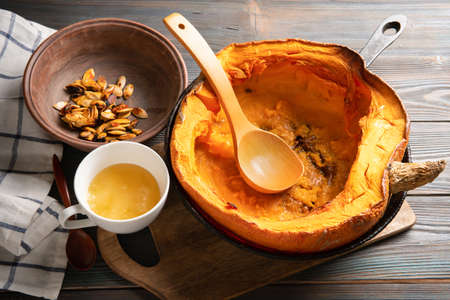 Baked pumpkin in a skillet with honey and seeds. Healthy eating. Vegetarian breakfast. Selective focus. Banque d'images