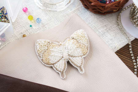 White butterfly on the table. Handmade beaded brooch on a wooden background Stock Photo