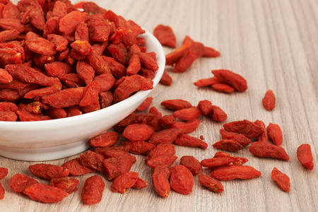 tibet bowls: Dried Goji berries placed in a white bowl and spread out on a wooden table Stock Photo