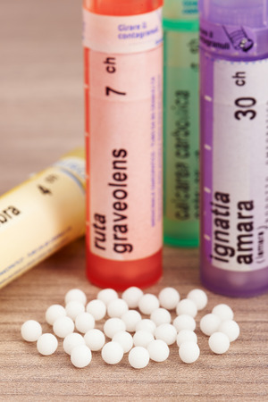 Homeopathic globules scattered around with their colored containers in the shape of tube on a wooden table