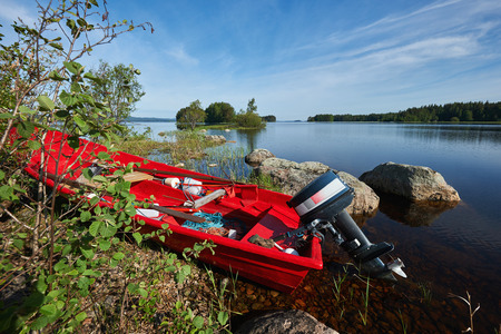 boat motor: Red boat motor at a lake in a Finnish spring day