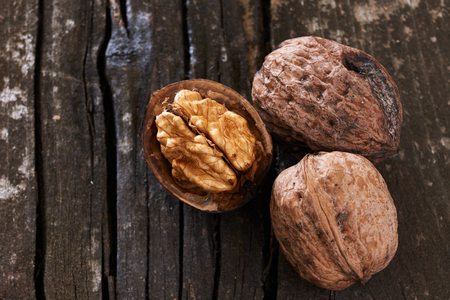 tree nuts: Three delicious freshly harvested nuts on an old wooden table Stock Photo
