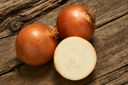 flavorings: Three delicious and fresh onions onions on an old wooden table