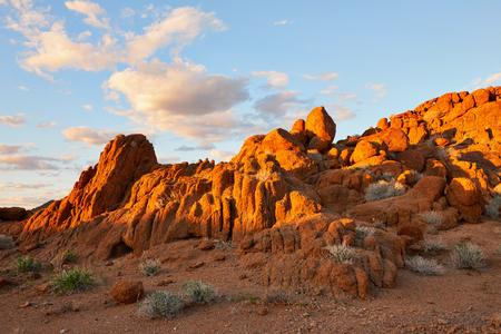大きな赤い岩とナミビアの夕日の風景