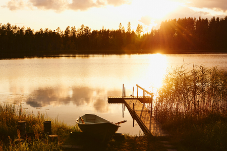 Summer sunset on the shore of a Finnish lake, with a small pier and a boat. Stock Photo