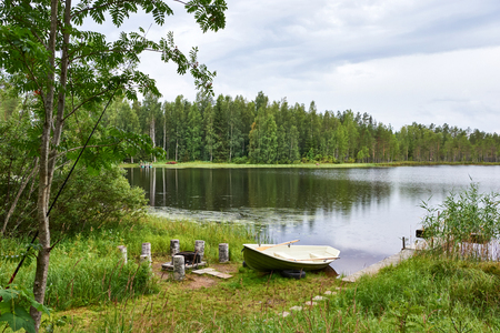 Summer landscape on the shore of a Finnish lake, with a small pier and a boat.