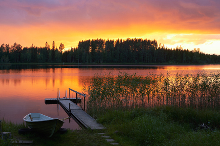 Summer sunset on the shore of a Finnish lake, with a small pier and a boat.