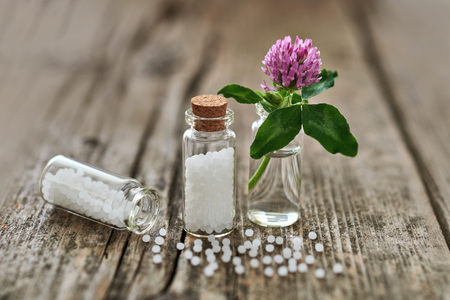 Homeopathic granules in small glass flasks, some granules scattered on the old wooden table and a small flower.