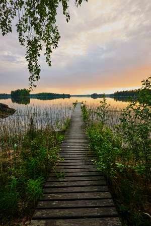 little pier at sunset in a Finnish lake under overcast sky 版權商用圖片
