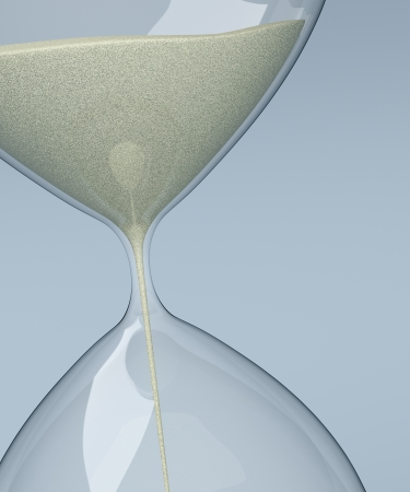 close up of sand flowing through an hourglass (3d render) photo