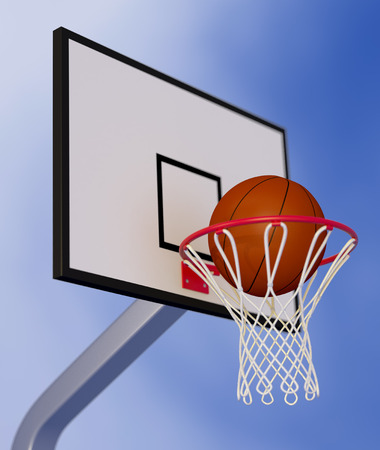 close-up view of a basketball hoop and a ball falling through the hoop, with a blue sky on background (3d render) photo