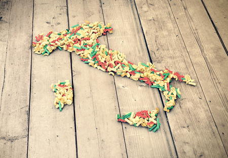 conceptual: the map of italy made with different shapes of pasta, wooden background (3d render)