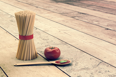 basil: bunch of spaghetti with a tomato and a ladle with tomato sauce, on wooden background, empty space at the right (3d render) Stock Photo