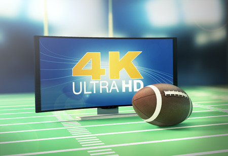 screen: curved tv with 4k on screen and a football ball, on a football field (3d render) Stock Photo