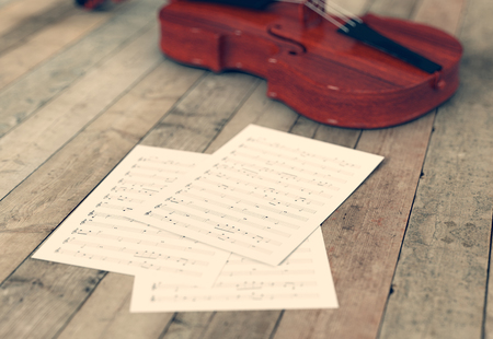 musical score: sheets music and a violin on wooden background (3d render)