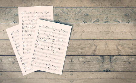 classical music: sheets music on wooden background, empty space at the right (3d render)