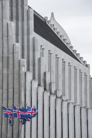 obrero: la famosa iglesia de Reykjavik y algunas banderas Foto de archivo