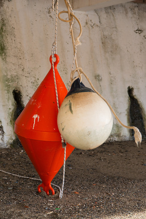 beach buoy: orange conical buoy and white spherical buoy hanging under a terrace on the beach