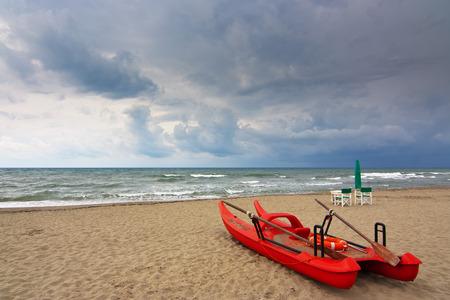 viareggio: lifeguard oar boat called in  italy pattino or moscone on the forte dei marmis beach in a cloudy day Stock Photo