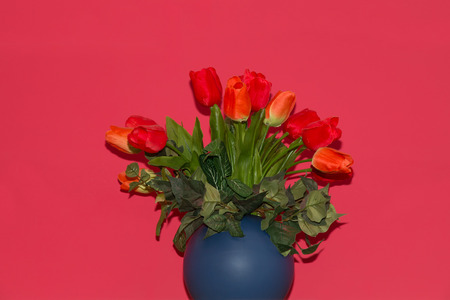 fale: bouquet of red artificial tulips in a blue vase red background