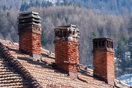 old gas stove: three old damaged chimneys made of bricks