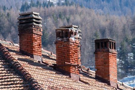 gas fireplace: three old damaged chimneys made of bricks