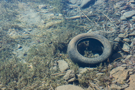 dumped: old car tire under the clear water of a mountain lake viewed from above Stock Photo