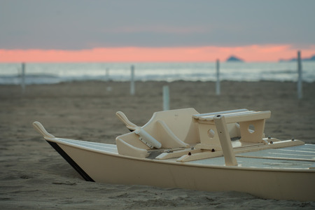 forte: wooden oar boat called in  italy pattino or moscone half buried by the sand on the beach of Forte dei Marmi at sunset Stock Photo