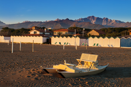 oar: wooden oar boat called in  italy pattino or moscone half buried by the sand on the beach at Forte dei Marmi, sea cabin and apuan alps in background