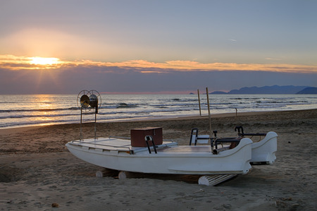 fiberglass: small fiberglass fishing boat on the beach at sunset in Forte dei Marmi Tuscany Stock Photo
