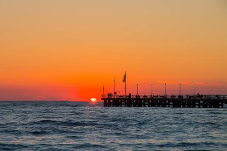 dei: Forte dei marmis pier at sunset,  people watching the sun    in a beautiful day. orange sky