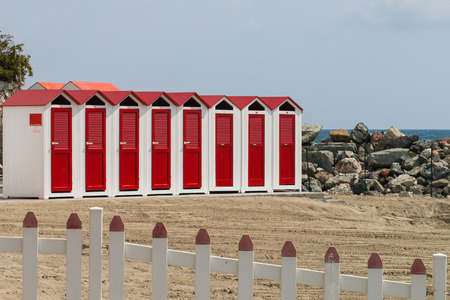 red and white beach cabins and fence in foreground in a spring sunny day photo