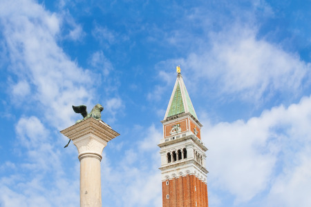 bell bronze bell: St. mark39s square column with lion39s famous bronze statues symbol of venice and bell tower in a sunny day blue sky some clouds