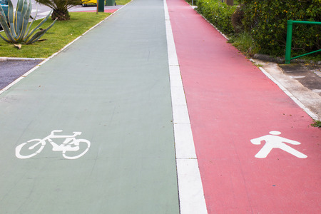 one lane sign: bicycle and pedestrians reserved lanes  made of green and red asphalt in forte dei marmi tuscany italy