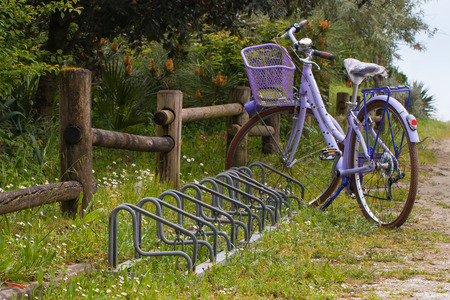 violet bike with basket and bicycle raks near a wooden fence in a dirt orad Stock fotó