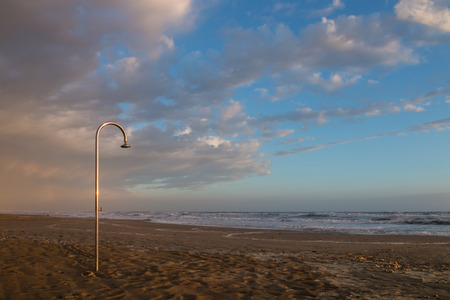 shorelines: stainless steel shower on the beach in a rough seas windy and cloudy evening