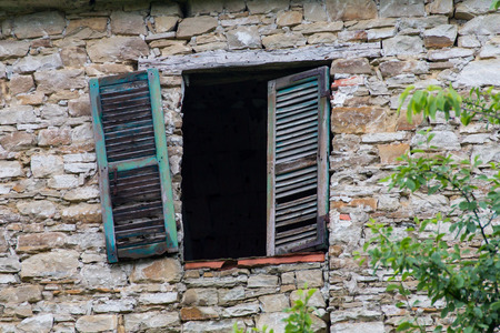 without window: Broken window with green wooden shutter and without glasses in a stone wall detail of an old  abandoned country house in italy