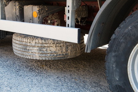 placed: dirty truck spare tyre placed horizontally under cargo bed loading area