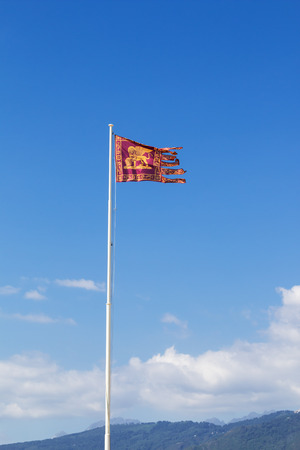 the merchant of venice: flag of the republic of venice waves in the wind on a tall pole against a blue sky with some clouds wooden hills in background Stock Photo